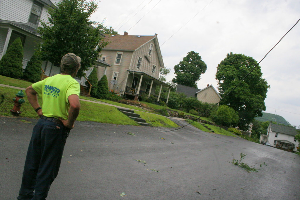 DPW worker Larry Harriso examines a downed power line that hangs across Prospect Ave. after a nearby tree ripped the line off the side of a house.