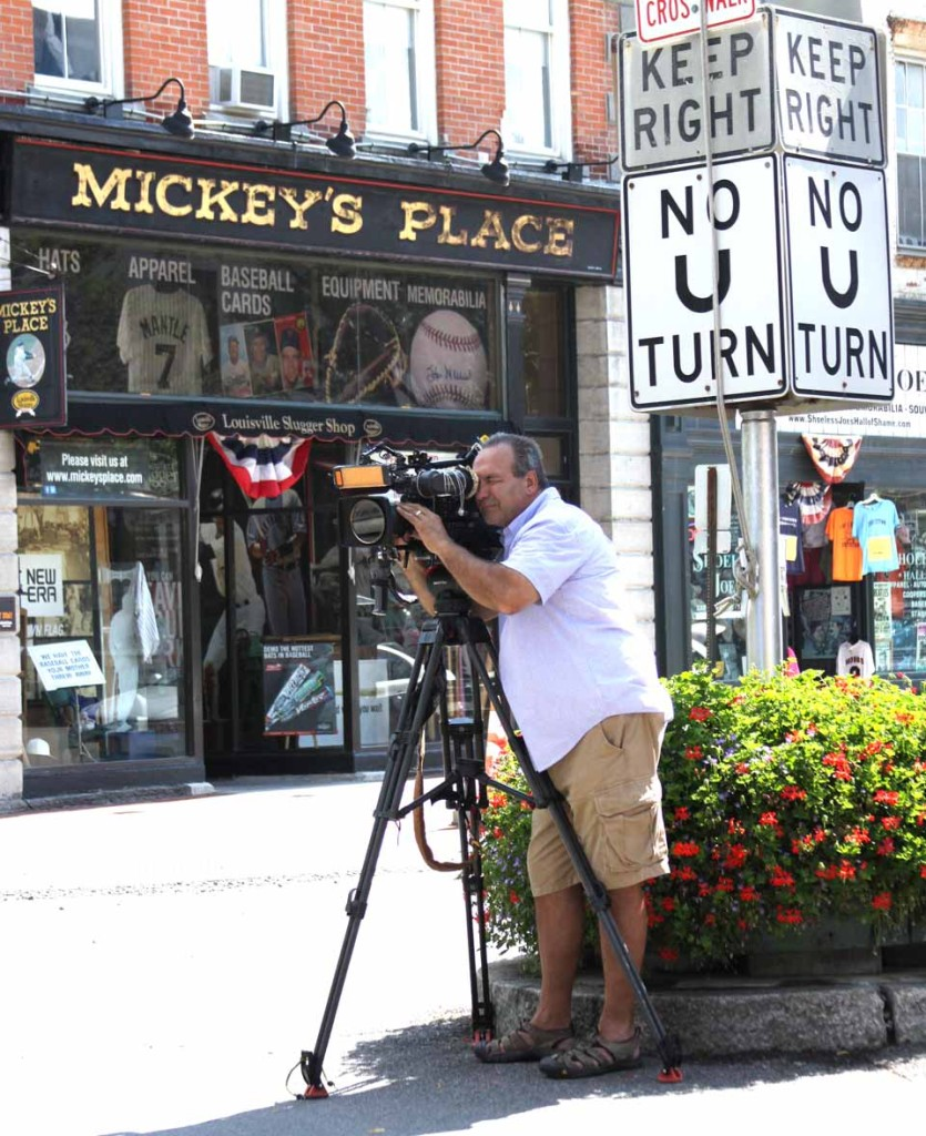 """CBS camera man Jim Zurich films a long view of Main Street a few minutes ago for areport on the 75th Hall of Fame Induction, which will air in the days before the big weekend begins on Friday, July 25, on """"This Morning,"""" the network's daily morning show with Charlie Rose. This shot included HoF Chairman Jane Forbes Clark and the Clark Foundation's Glenn Perrone passing in a convertible. Zurich said the crew will be in the village throughout the day. (Jim Kevlin/allotsego.com)"""