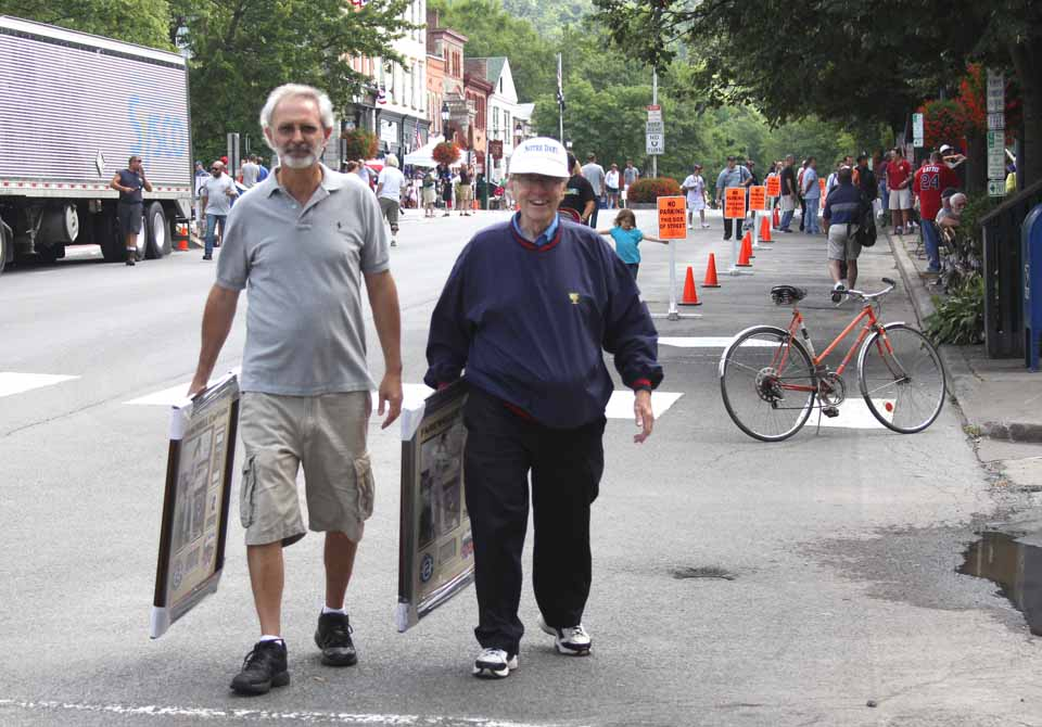 Donald Moore, Endicott, a 23-year member of the Baseball Hall of Fame, traverses Cooperstown's Main Street this morning, soaking in the mounting sizzle at the 75th anniversary weekend gets underway.  With him is pal Tom Olshefski.  The street was closed to traffic, and some MLB stars were already signing autographs.  (Jim Kevlin/allotsego.com)
