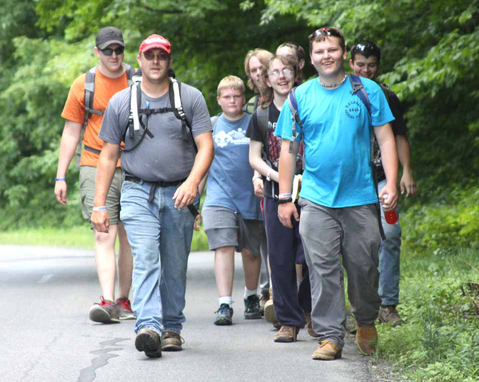 Drivers along County Route 35 between Portlandville and Milford this afternoon would have happened upon this group of Scouts from the Crumhorn camp completing a 10 mile hike required for the hiking badge.  In the front are Scoutmaster Samuel Miller, left, of Fultonham, Montgomery County, and Damian Laird, Sidney.  Behind them, from left, are Andrew Work, Fultonham, Logan Doucas, Cooperstown, Eric Buskey, Fultonham, Chase Sutliff, Sidney, Christian Buskey, Fultonham, and Irving Skowjoe,Oneonta.  (allotsego.com)