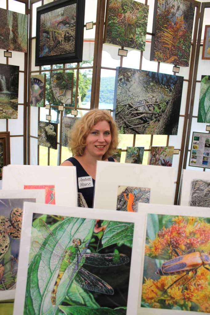 "Springfield Center artist Andrea House sits amid nature, depicted in her works, at today's ""Art By The Lake"" that continues until 5 p.m. on the back lawn of The Fenimore Art Museum.  (Jim Kevlin/allotsego.com)"