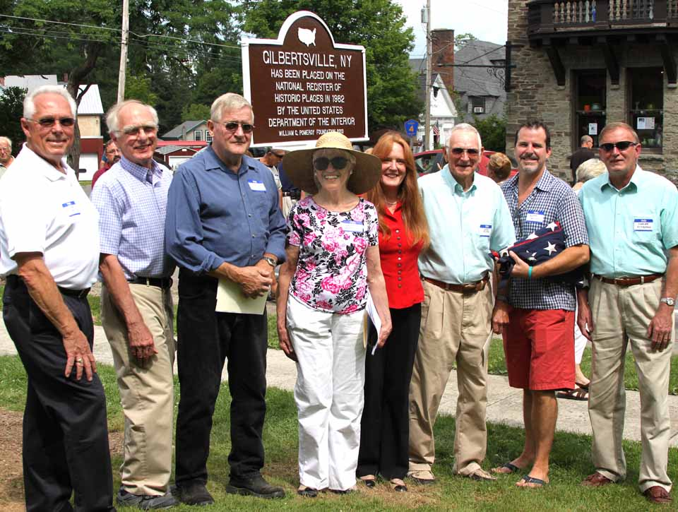 Decades after the whole Village of Gilbertsville was placed on the National Register of Historic Places, a plaque was unveiled this afternoon across from the Major's Inn commemorating that achievement.  Also celebrated this afternoon was the 125th anniversary of the village post office. Among those at the unveiling were, from left, Assemblyman Clifford Crouch, R-Bainbridge; Larry Armstrong, treasurer, Village Improvement Society; Village Mayor Ken Nolan, Village Historian Leigh Eckmair, who obtained funding for the marker from the Pomeroy Foundation; Victoria Bonner, postmaster; Glenn Voster, VIS vice president; Jonathan Dokuchitz, VIS; and Town of Butternuts Supervisor Charles Eckelmann. (Jim Kevlin/allotsego.com)