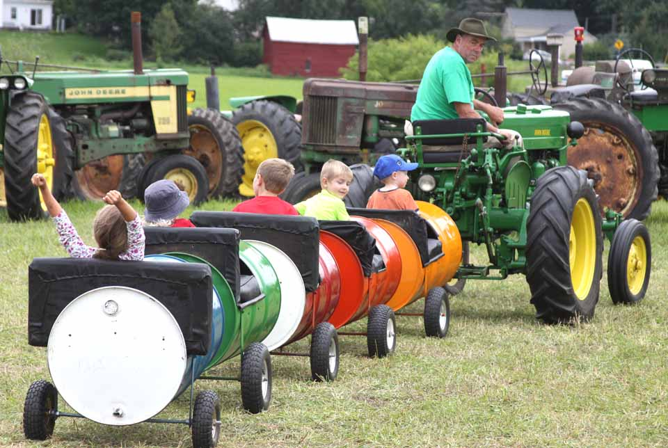 "Ron Van Buren, East Worcester, entertains youngsters on his tractor-driven ""train"" today at Roseboom Antique Power Days, featuring more than 100 tractors, new and old, from around the region, plus food, Amish ice cream (and peaches) and other delights.  An enthusiastic Allie Ritchie, 6, of Cooperstown, cheers in the caboose.  The annual weekend's main event is at 1 p.m. Sunday, the tractor parade through Roseboom's streets.  (Jim Kevlin/allotsego.com)"
