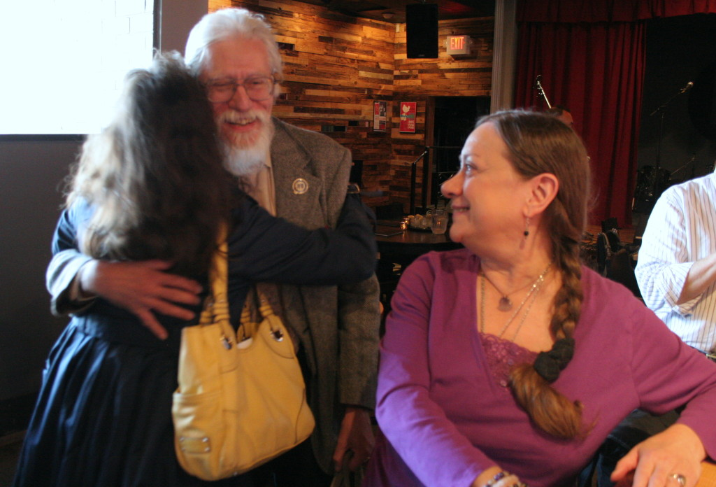 Retiring SUNY Music Professor Renee Prins, middle, is embraced by friend Colby Thomas, left, as his partner Marilyn Roper, right looks on. The B-Side Ballroom hosted a retirement party get-together for Prins on Tuesday afternoon.