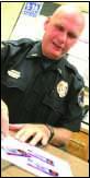 Lt. Doug Brenner examines the cache (Ian Austin/HOMETOWN ONEONTA)