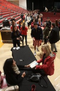 SUNY freshman Anastasia Rubertone was one of the first students to get her copy of Persepolis signed by Marjane Satrapi. Behind them, a line of faculty and students stretches across the alumni field house.