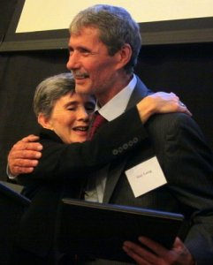 Diane Aaronson, Chairperson of the FOF Board, embraces Gary Laing after awarding him the Community Leadership award for his work and variety of programming he has brought to Damaschke Field.