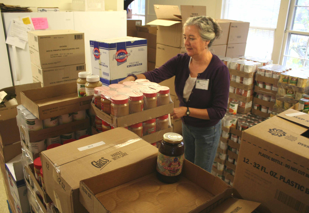 Cooperstown Food Pantry manager Audrey Murray stacks boxes of food in the new ground-level quarters at the Cooperstown Presbyterian Church offices, 25 Church St., this morning.  The renovations of the new quarters and moving inventory from the building's basement was completed yesterday.  Audrey said $5,000 was raised to match a Scriven Foundation grant, and that assisted the project's completion.  The new quarters include a waiting room for clients. (Jim Kevlin/allotsego.com)