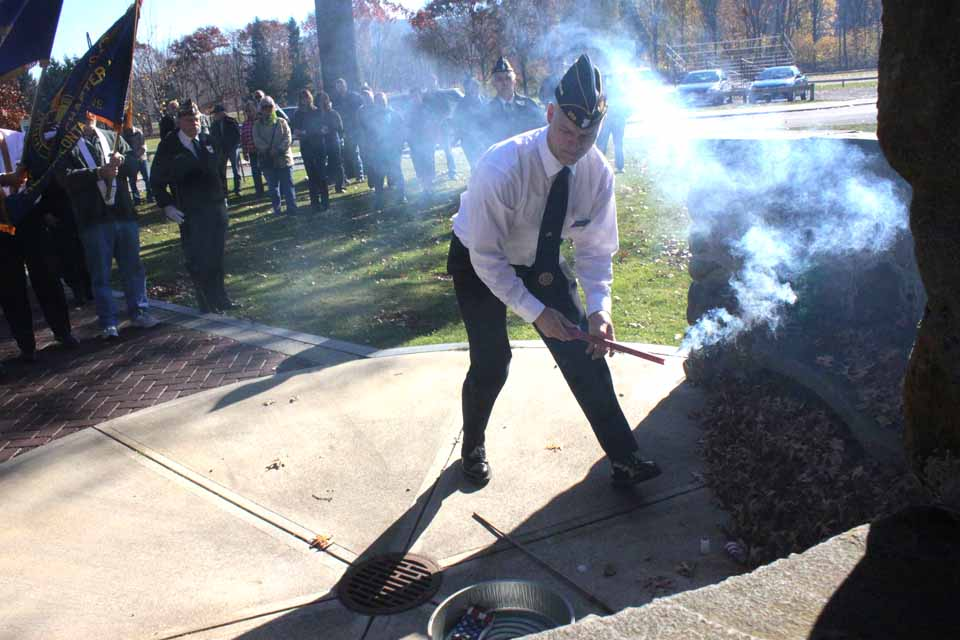 Oneonta American Legion Commander Len Carson ignites the ceremonial burning of the American flag this morning during Veterans Day ceremonies at the end of the Memorial Walkway in Neahwa Park.  Veterans from Greater Oneonta and beyond attended the annual exercise.  (Ian Austin/allotsego.com)