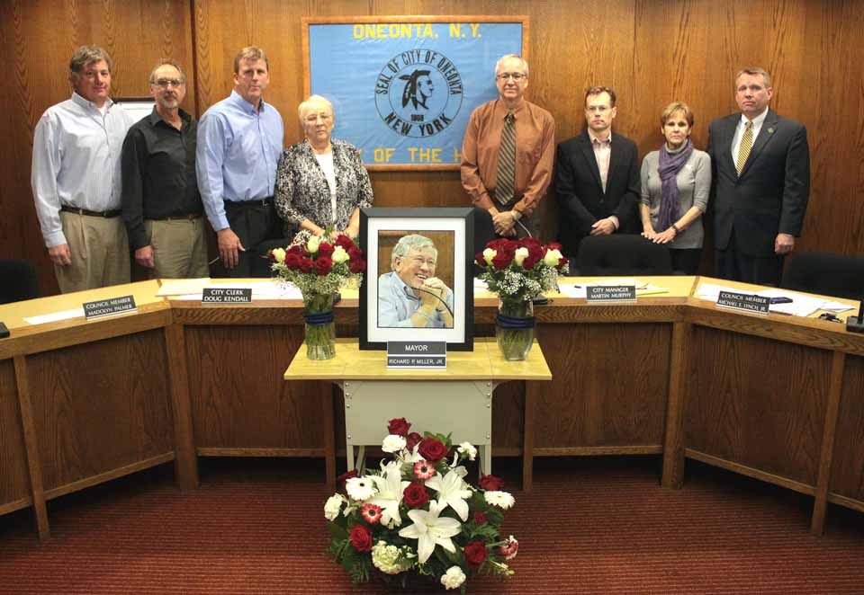 This evening's Oneonta Common Council meeting, the first since Mayor Dick Miller's passing, began with a moment of silence amid a tribute set up in his memory.  From left are Council members Chip Holmes and Bob Brzozowski; Russ Southard, the new mayor; and Council members Madolyn Palmer, Larry Malone, David Rissberger, Maureen Hennessy and Mike Lynch.  (Ian Austin/allotsego.com)