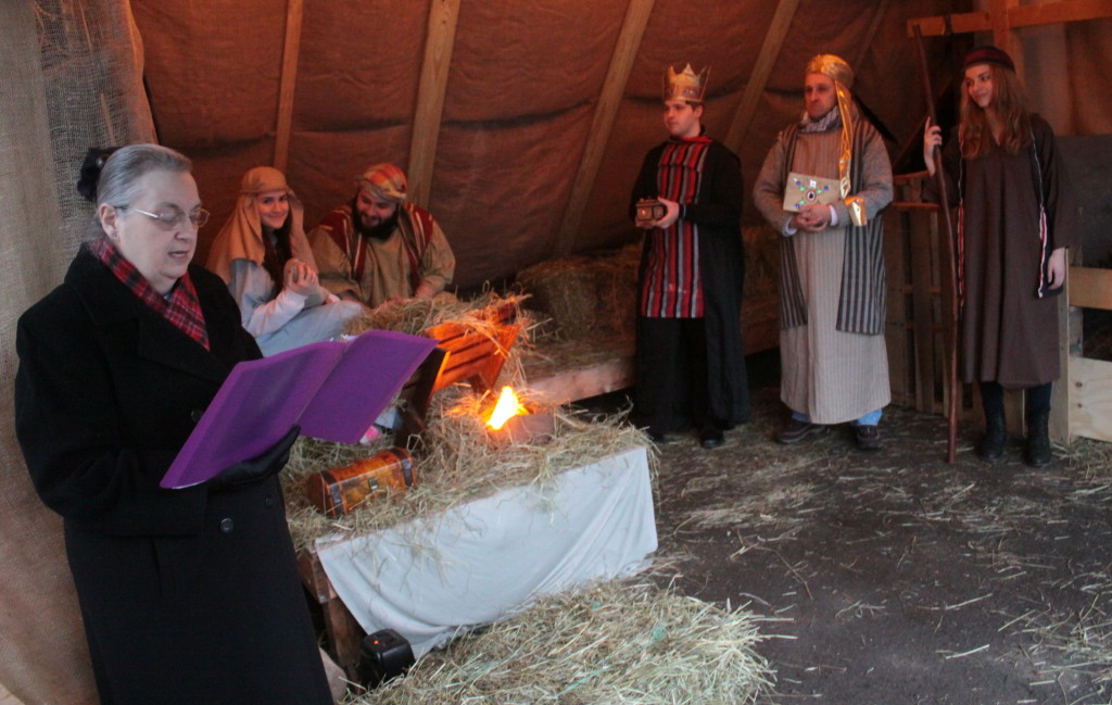 Carol Effner, left, reads the story of Christmas at the living manger scene that was put on my the St. James church on Christmas Eve. The stable, which was constructed in a carriage house behind the The Turning Point on Elm St.  featured Sarah Hunter and James Crosby as Mary and Joseph, Greg Hunter,  Fred Healey and Tarrah Smith as the 3 wise men, along with several alpacas and a donkey.
