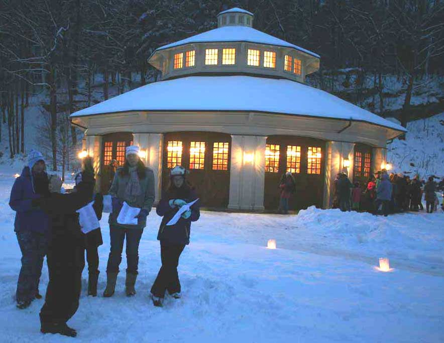 Today's (relatively) balmy weather drew what may be a record crowd to The Farmers' Museum Candlelight Evening, a centerpiece of the local Christmas season. It continues until 7, so you still have a chance to get out there. Here, 4H singers – from left, Rogan and Tammy Graves from Richfield Springs, and Owen, Cindy and Abigail Allen from West Winfield– perform in front of the Empire State Carousel as the evening falls. (Jim Kevlin/allotsego.com)