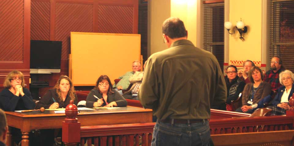 Cooperstown Mayor Jeff Katz asks the county Board of Representatives this evening for tourism-impact for his village, the city and town of Oneonta, and the Town of Hartwick.  Listening, from left, are county board chair Kathy Clark, R-Otego, Clerk of the Board Carol McGovern,  and county Reps. Don Lindberg, R-Worcester, Ed Frazier, R-Unadilla, Janet Hurley Quackenbush, R-Town of Oneonta, Gary Koutnik, D-Oneonta, Ed Lentz, D-New Lisbon,  and Linda Rowinski and Kay Stuligross, both Oneonta Democrats.  (Jim Kevlin/allotsego.com)
