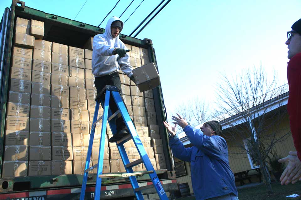 At this hour, proprietor Gene Marra and his crew at Cooperstown Distillery are unloading 10,000 bottles at the Railroad Avenue plant.  Marra, whose distillery is celebrating its first anniversary this weekend, said the truckload may last for nine months.  Here, Rory Gallagher, atop ladder, tosses a box down to his boss.  (Jim Kevlin/allotsego.com)