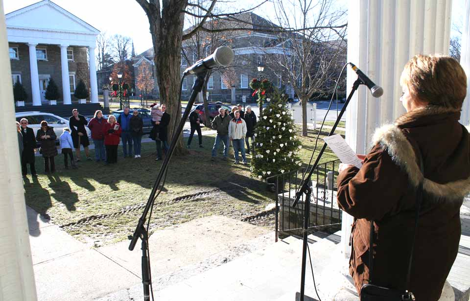 "Lola Rathbone, president/CEO, Catskill Area Hospice, welcomes 40 people who gathered a few minutes ago for the lighting of a Tree of Life, bearing handmade heart ornaments in memory of lost loved ones, in front of 22 Main St., Cooperstown's village hall.  The trees are a tradition in Oneonta and Cobleskill, but this is Cooperstown's first, the idea of Mary Margaret Sohn.  The A Coopella group sang Christmas carols, and Bruce Markusen read a poem, ""Hospice Lights.""  (Jim Kevlin/allotsego.com)"