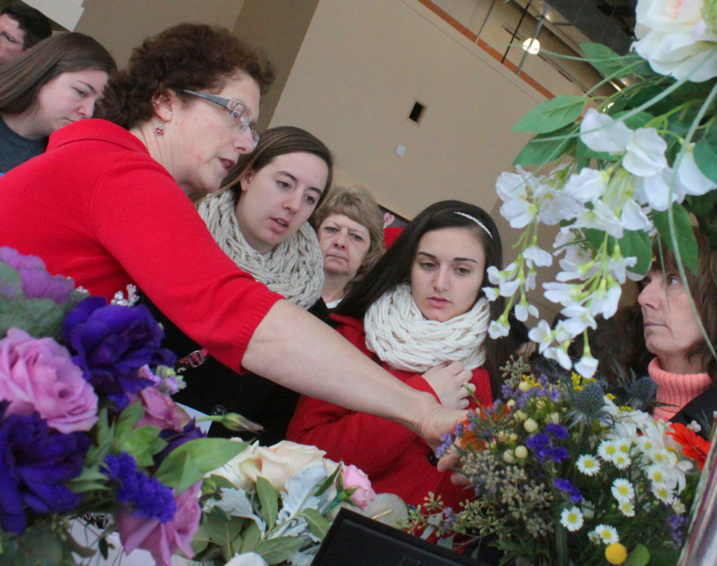 Claire Satriano, Cooperstown, left, shows bride-to-be Lea Lopresti, her sister Allie and mother Lois, all of Norwich, some of the wedding floral options they have at Mohican Flowers, who were one of many vendors at the I Do Bridal Expo at Foothills on Sunday afternoon.