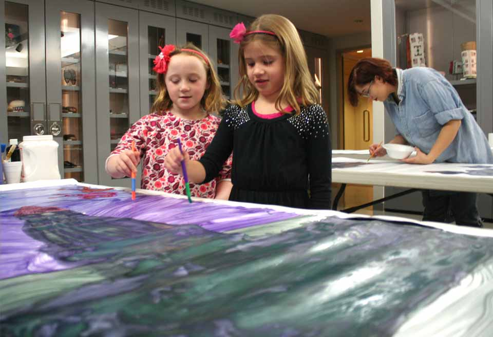 Kylie Sala, left, and Allison Swart, both 7 and second-grade classmates at Cooperstown Central School, put the finishing touches on their panel for a mural being painted over the weekend at The Fenimore Art Museum.  The mural will be completed Sunday between 10 and 4.  (JIm Kevlin/allotsego.com)