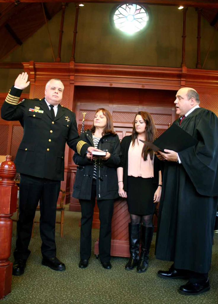 Sheriff Richard J. Devlin Jr. is sworn in for his third term by state Supreme Court Judge Michael V. Coccoma.  Bearing witness are his wife Laurie and their daughter.