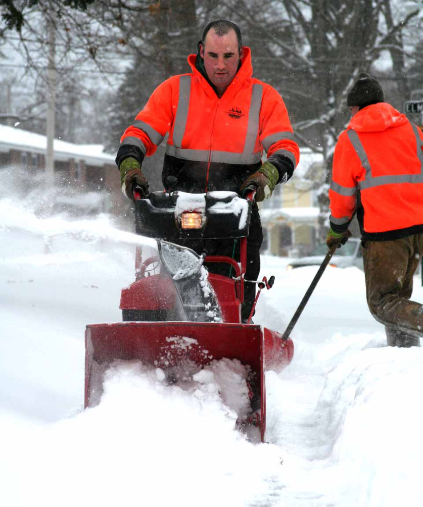 The Leatherstocking Corp.'s Justin Romero snow-blows the sidewalk at Chestnut and Delaware a few minutes ago.  (Jim Kevlin/allotsego.com)