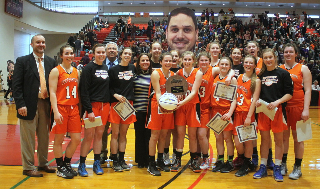 The triumphant Cooperstown Lady Hawkeyes basketball team is headed to the Final Four after crushing Watkins Glen 46-34 in the Class-C quarterfinals at the SUNY Dewar Union Field House earlier this afternoon.  Though assistant coach Matt Hazzard could not be with them, the team brought his smiling face along for good luck. (Ian Austin/allotsego.com (Ian Austin/allotsego.com)