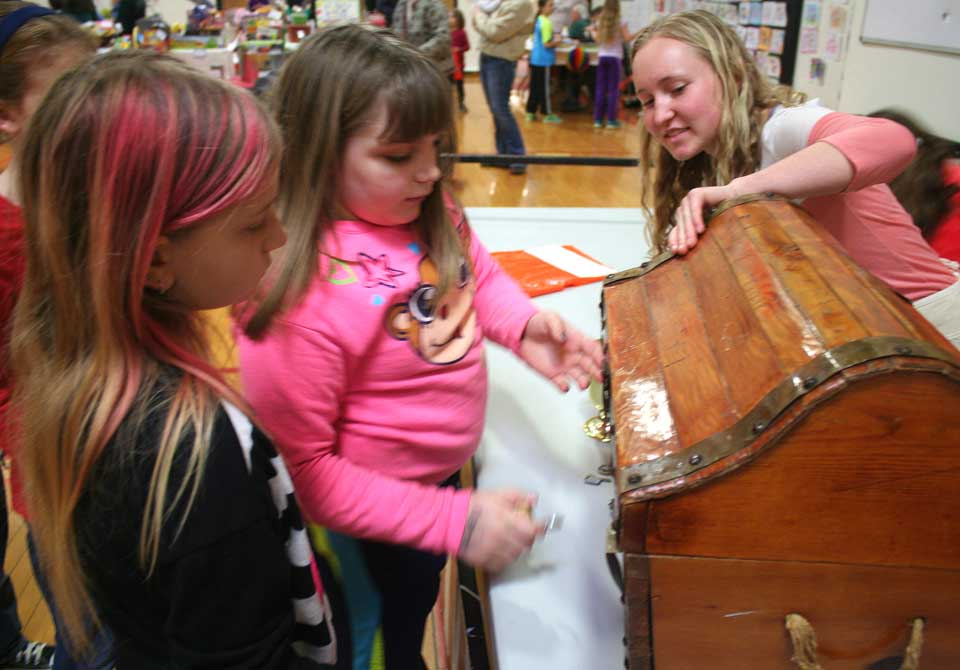 Gabi Ragozinne picks the key that opens the treasure chest at today's Crayon Carnival, underway in Cooperstown High School's Bursey Gym.  Gabi and her friend, Shayanne Couse, are fifth graders in Oneonta schools.  Overseeing the booth -- one of many -- is Margie Knight.  Bouncing games, food and a tag sales are part of the fun.  (Jim Kevlin/allotsego.com)