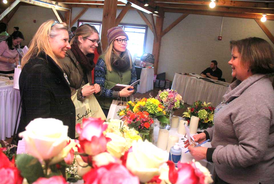 Kathy Kroll, Oneonta, of Coddington's Flowers, right, talks floral options with Ellen Tillapaugh Kuch, Cooperstown, and her daughters Rachel and Maggie.  They were among attendees at the House of Brides Love Is In The Air Bridal Show, hosted at The Carriage House, Southside Oneonta, on Sunday afternoon.  (Ian Austin/allotsego.com)