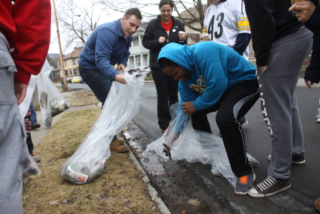 Hartwick students Will Von and Morgan Breland retrieve trash from the curb of Pine St. on Saturday morning as part of the 3rd Ward Volunteer Cleanup sponsored by AOπ and Phi Kappa Psi. (Ian Austin/ allotsego.com)