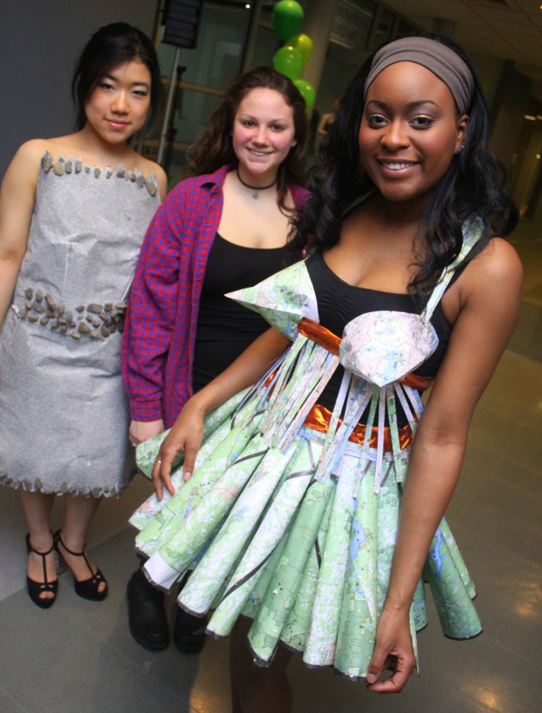 "SUNY Oneonta students celebrated Earth Day Thursday afternoon with the fashion show featuring recycled materials at the Human Ecology building. Here, sophomore Kirsten Bellek, center, stands with her models Yukiyo Masuva, left, and Deniece Luckey, right. The dresses, titled ""Set in Stone"" and ""Around the World,"" were made from paper, stone, maps and other recycled materials to create wearable works of art. (Ian Austin/allotsego.com"