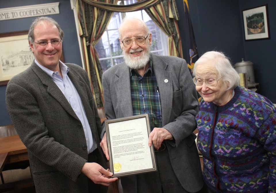 Cooperstown Village Historian Hugh MacDougall was presented a certificate of appreciation in recognition of his contribution to Otsego County history at a reception in Village Hal this evening following the swearing-in of Trustees Falk and Dean.  Making the presentation is Mayor Jeff Katz, left.  At right is Hugh's wife Eleanor.  (Ian Austin/allotsego.com)