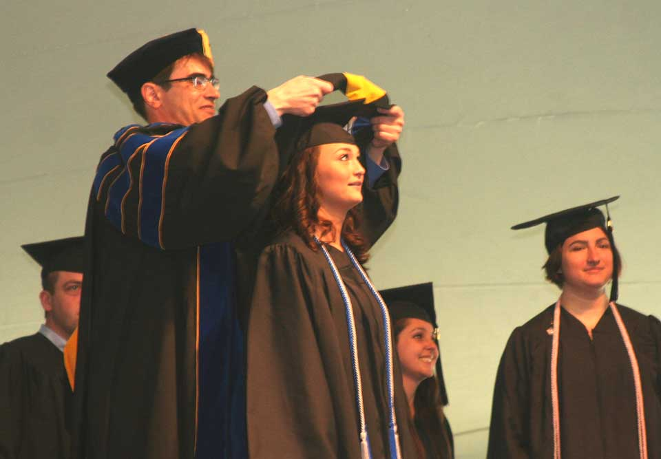 Tara Ann Wilson of Oneonta, a business administration major, receives the shawl that signifies her new status as a college graduate during today's 84th Commencement on Oyaron Hill, where the school relocated after operating in Hartwick Seminary since 1797.  (allotsego.com)