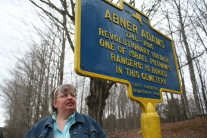 Deb Mackenzie examines Revolutionary War veteran Abner Adams' marker in one of her favorite historic resting places.  (allotsego.com)