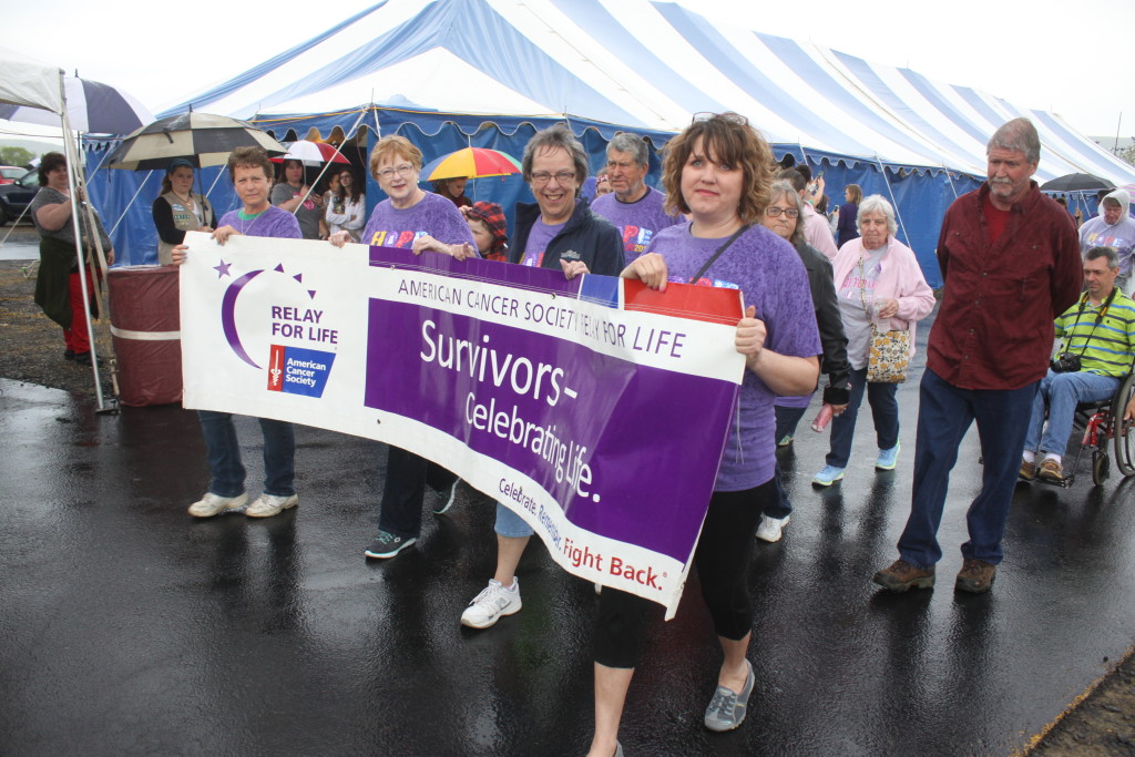Area Cancer survivors Allison Wilber, Burlington Flatts, Joyce Boyde, Fly Creek, Janet McCarthy, East Springfield, and Susan Carpenter, Edmestone carry the survivors' banner during the Survivors' lap of the Relay for Life walk hald at the Cooperstown Dreams Park on Friday evening. (Ian Austin/allotsego.com)
