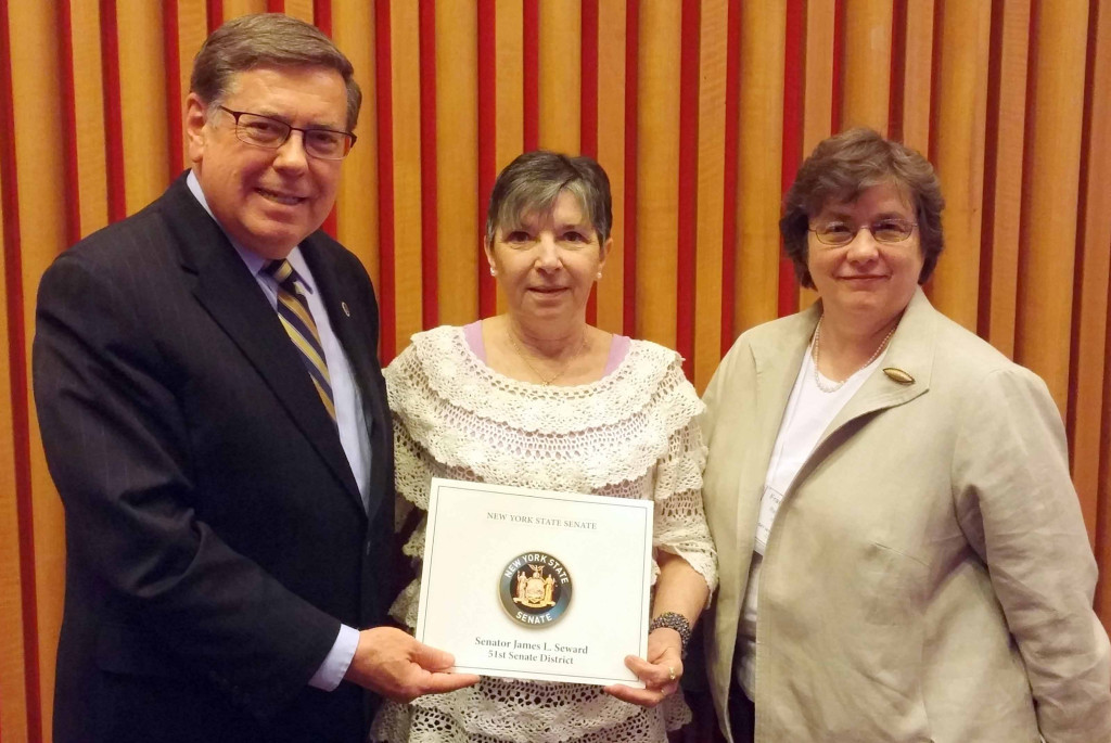 Senator James L. Seward honors Sheila Serbay, one of five senior citizens recognized at the Office For the Aging Senior Citizen Day Celebration.  With her is Frances Wright, director of the Otsego County Office for the Aging.