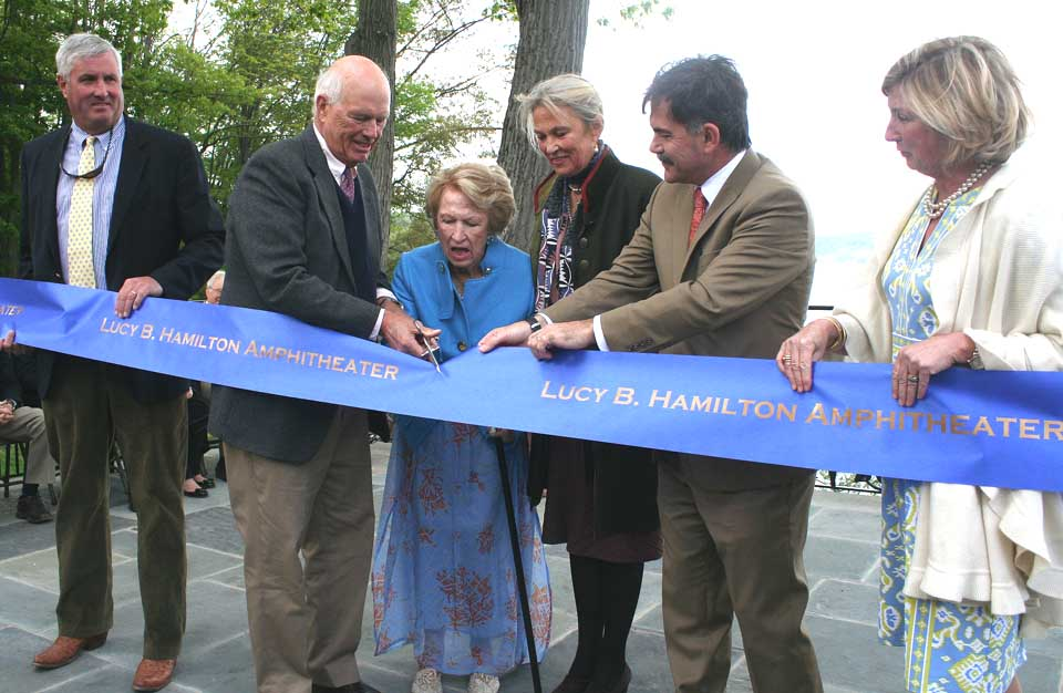 Bunny Hamilton cuts the ribbon on the lakeside amphitheatre named in her honor.  She is flanked by, from left, her husband, Dr. Lewis Hamilton, her daughter, Lucy Townsend, and NYSHA President Paul D'Ambrosio.   Holding the ribbon are son Lyman Townsend and NYSHA Trustee Shelley Graham.  (Jim Kevlin/allotsego.com)