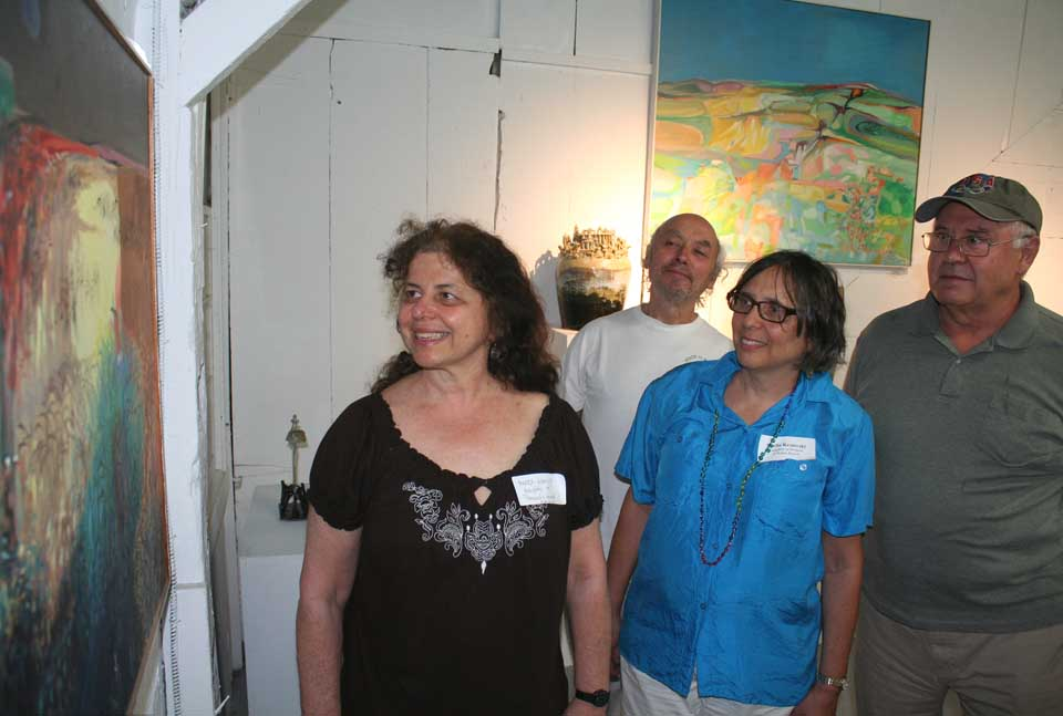Bernie and Honey Kassoy's daughter and their husbands are at the Smithy-Pioneer Gallery's first opening of the summer at this hour to view paintings by both their parents, who were decades-long members of the artists' group.  From left are Merry Kassoy and her husband, Rafe Bustin, of Bedford, Mass., and Sheila and Dimitar Krstevski of Westchester County.  The elder Kassoys summered at their studio near Garrattsville for years.  (Jim Kevlin/allotsego.com)