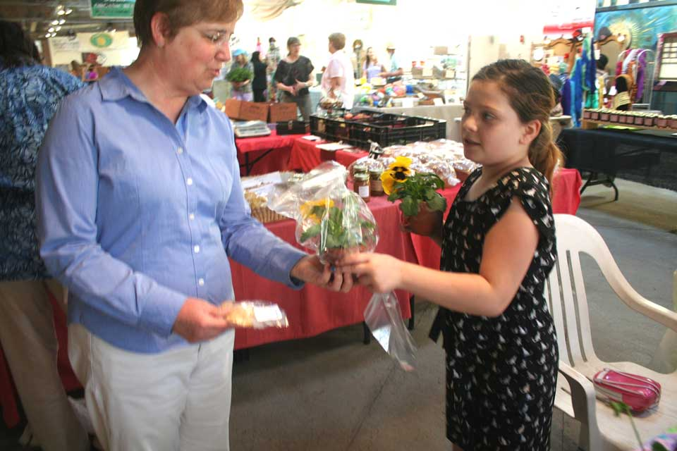 In what's become something of a Mother's Day Weekend family tradition, Lilly Ryan, 9, of Cooperstown, hands out flowers to mom Betsy Jay this morning at the Cooperstown Farmers' Market.  She expected her sisters to join her later in the morning.  Betsy, who is chaplain at Bassett Hospital, expects calls Sunday from her children, Emily,  in Ashville N.C., Derek in Naples, Fla., and Ian, in Manhattan.  (Jim Kevlin/allotsego.com)
