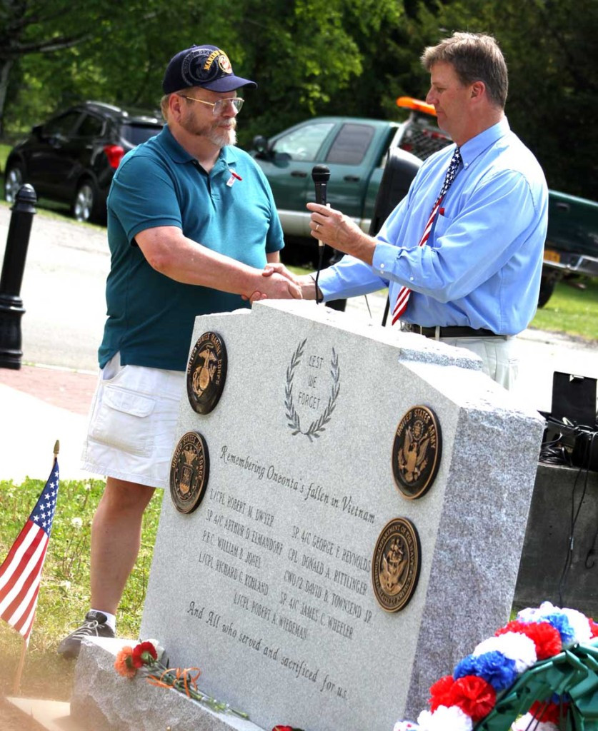 Oneonta Mayor Russ Southard, right, congratulates Vietnam-era veteran Gene Schmit, an OHS grad now living in Unadilla, for his successful drive to raise funds for a Vietnam monument dedicated this morning in Neahwa Park.  Schmidt raised $6,200 last fall to remember the nine OHS grads who died in Vietnam; he knew six of them personally; three were in his class.  (Ian Austin/allotsego.com)