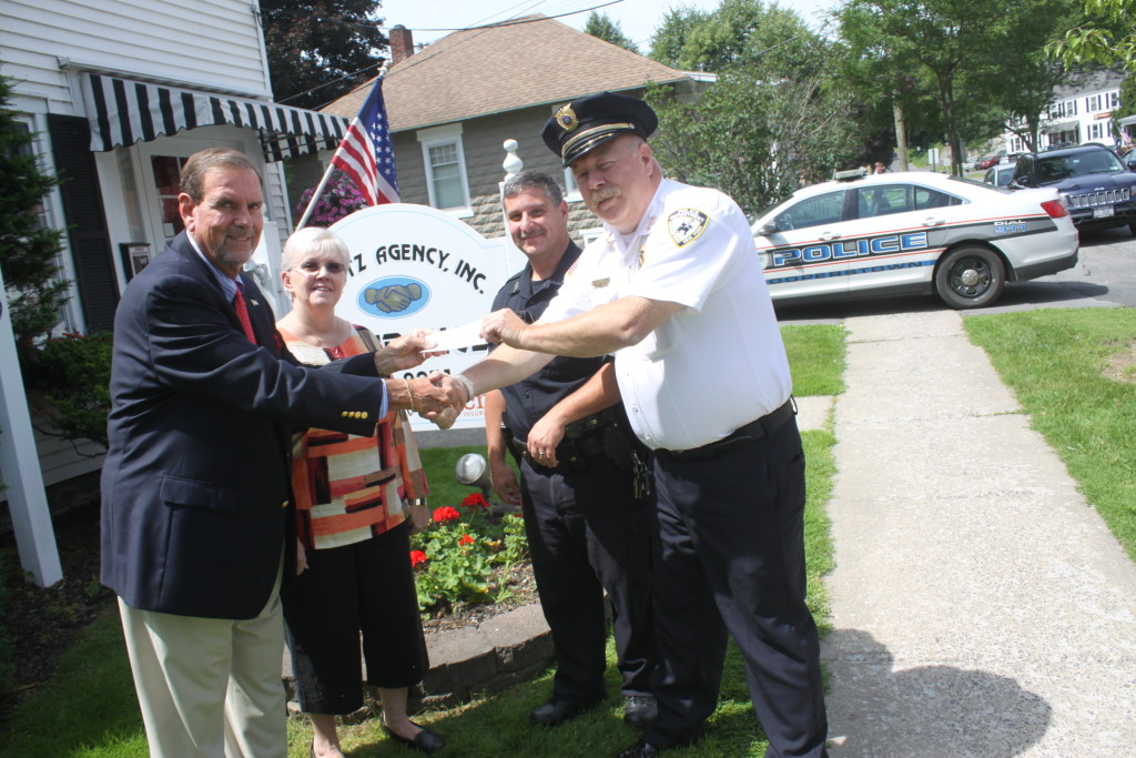 Steve Bieritz, of the Bieritz Insurance Agency of Cooperstown, hands Chief Michael Covert a check for $2,914 to Chief to purchase four Body Worn Cameras for his officers.  The cameras, which will be turned on during all arrests, calls and stops. Also pictured are Sally Bieritz and Patrolman Kevin Voce.