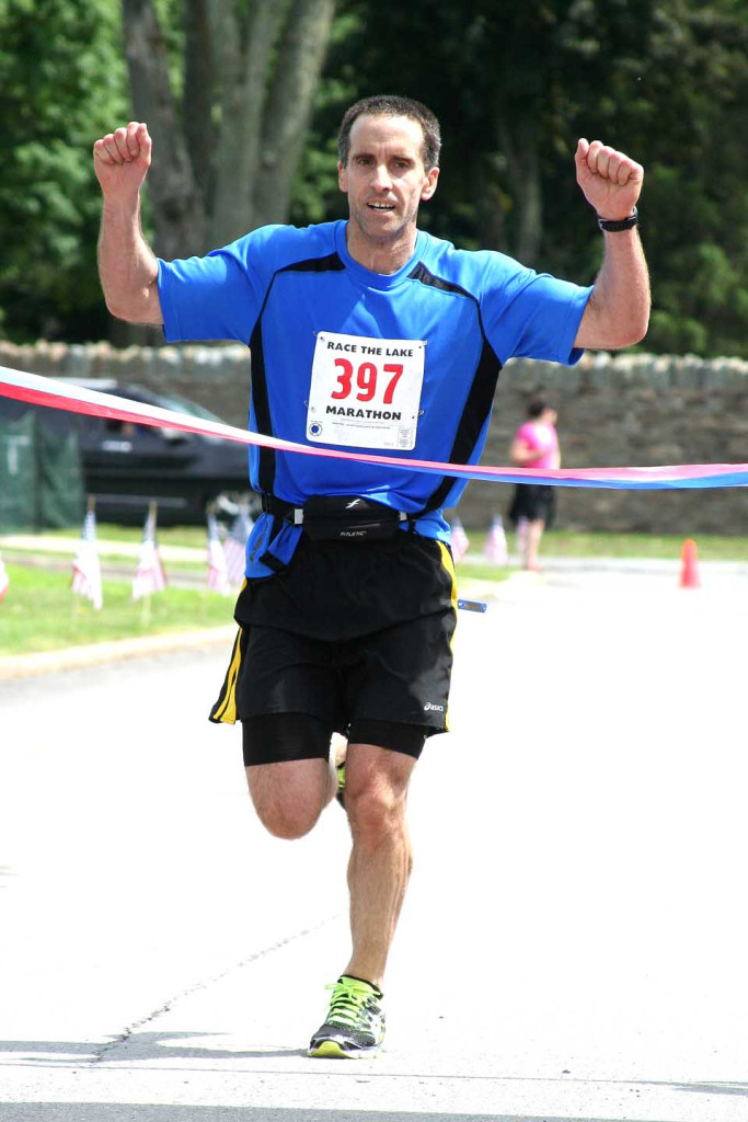 Greg Mandak of Camp Hill, Pa., wins the Race the Lake Marathon a few minutes ago, breaking the ribbon at the Clark Sports.  The half-marathon winner was Justin Spring of New York City, who is attending Bassett's medical school locally.   A total of 336 runner circulated Otsego Lake this morning, up from 148 in 2014, the first year.  (Jim Kevlin/allotsego.com)