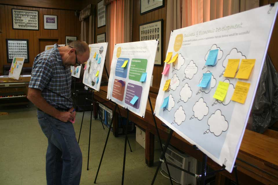 """Mohican Farms manager Bob Sutherland works his way around the """"idea stations"""" at today's Community Open House at the Cooperstown fire hall on Chestnut Street.  Residents' view are being collected on a range of topics – there are 16 """"idea stations"""" – that will be reflected in the updated Comprehensive Master Plan under preparation.  The open house continues through 7 p.m. today.  All are welcome (Jim Kevlin/allotsego.com)"""