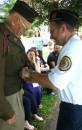 Laurens Legion Commander Jack Nelson helps button Brindle's Eisenhower jacket.