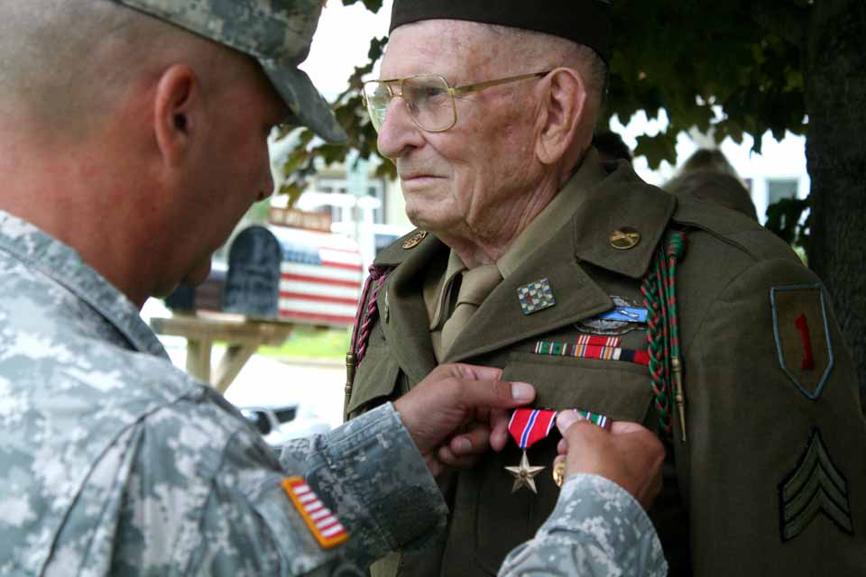 Army National Guard Col. Carlton Cleveland pins a Bronze Star on Staff Sgt. William Brindle's chest this morning in front of the Laurens American Legion, 60 years after he helped halt the German counterattack at the bridge over the Rhine at Remagan.  (Jim Kevlin/allotsego.com)