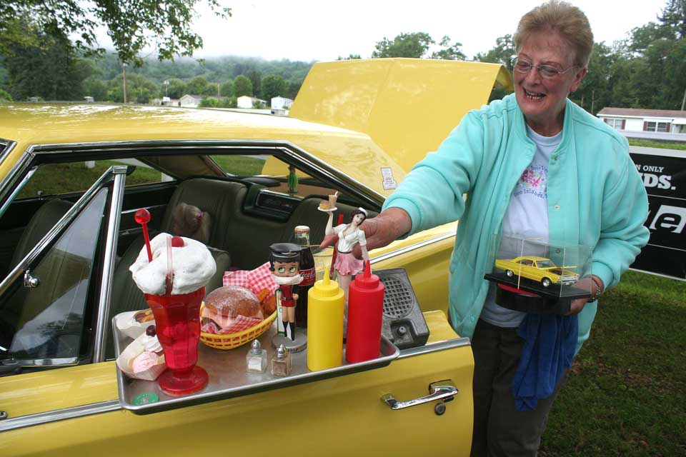 Yvonne Dewitt of Hobart helps set up husband Alfred's 1966 Plymouth Sports Satellite this morning at the first annual Father's Day Celebration Car Show & Swap Meet on Route 7 west of Oneonta.  Hometown Auto proprietor Keith Liggett took on the Father's Day tradition after the Reminiscers' Car Club decided to let its annual Neahwa Park show lapse.   The crowd was forming this morning despite threatening weather – in fact, the sun almost broke through the clouds at a couple of points.  First 150 dads to register will receive a free Brooks BBQ lunch.  (Jim Kevlin/allotsego.com)