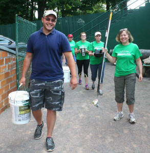 Doubleday Field manager  Quinton Hasak leads a group of Tourism Cares volunteers into the field this morning.