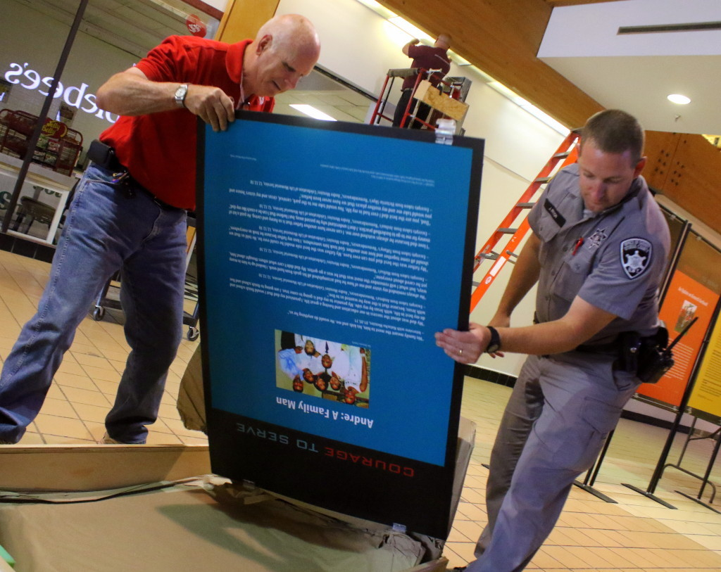Richard Devlin, Sr., left, and officer Jason Ritton take out panels for a new display at the Southside Mall dedicated to officers in NY State who have lost their lives to drunk drivers. Their stories and personal artifacts will be on display until the end of the month.