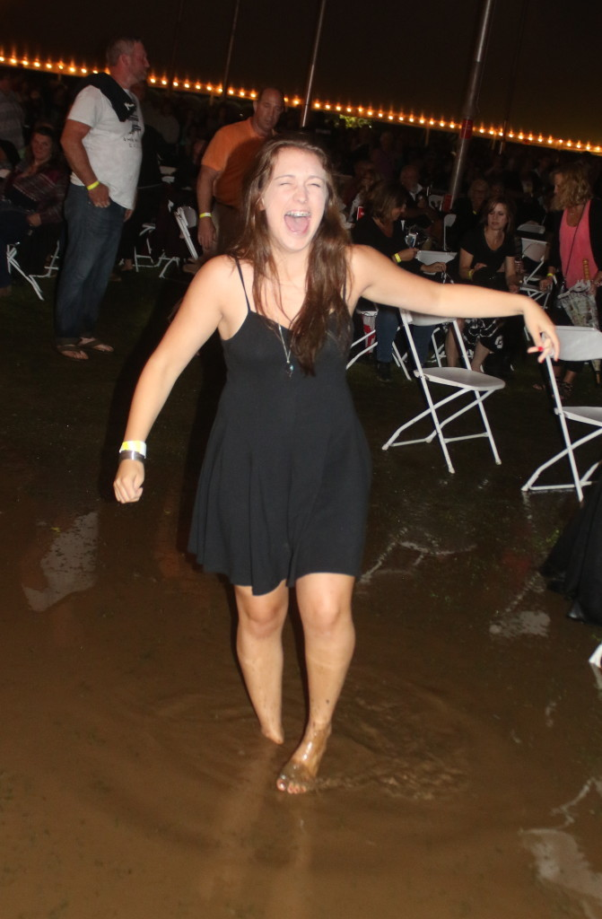 Erin Lutz, South Kortright, laughs as her shoe is sucked off in the ankle deep mud inside the concert tent. (Ian Austin/ allotsego.com)