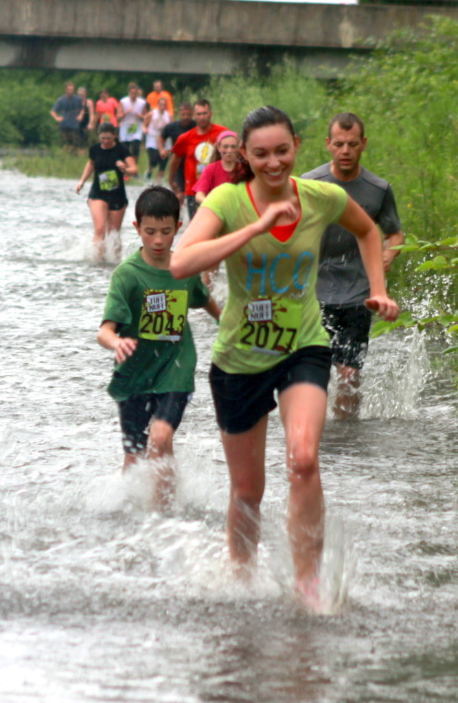 540 Runners in this morning's Tuff eNuff proved they had what it takes to brave obstacles and driving rains, but conditions forced the parade to be postponed until noon on Sunday, July 5.  Some events in Neahwa Park have been cancelled, but vendors and music are still playing. Here, Oneonta accountant Elizabeth Johnson leads a group of runners down the Mill Race in Neahwa Park during the 2nd wave of the recreational race. (Ian Austin/ allotsego.com