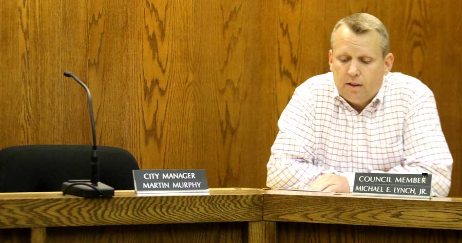 Council member Mike Lynch reads a resolution to suspend City Manager Martin Murphy in absentia. Murphy was in Saratoga, where his first granddaughter was born Thursday, the day he was asked to resign. (Ian Austin/allotsego.com)