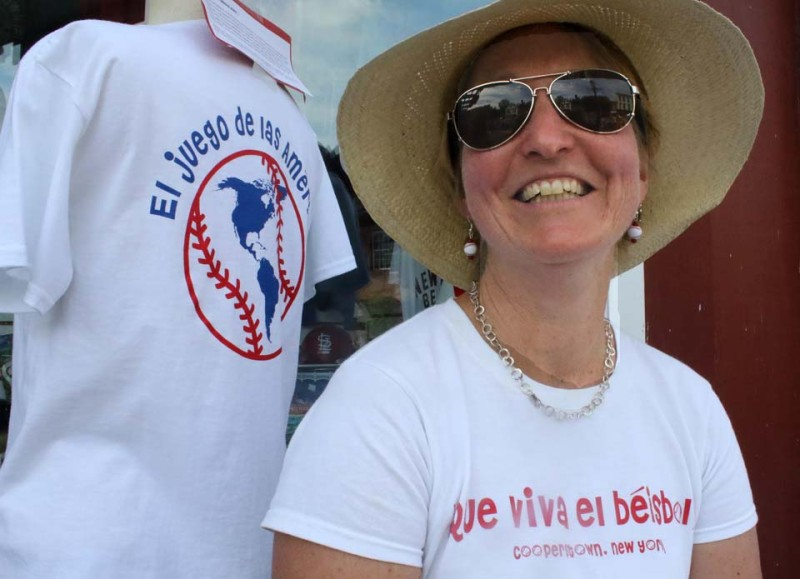 CCS Spanish teacher Suzy Knight is selling T-shirts celebrating baseball's popularity beyond North America.  Today, she is in front of F.R. Woods, 61 Main St., Cooperstown, but usually the shirts may be found at Barnyard Swing, Hartwick Seminary.  (Jim Kevlin/allotsego.com_