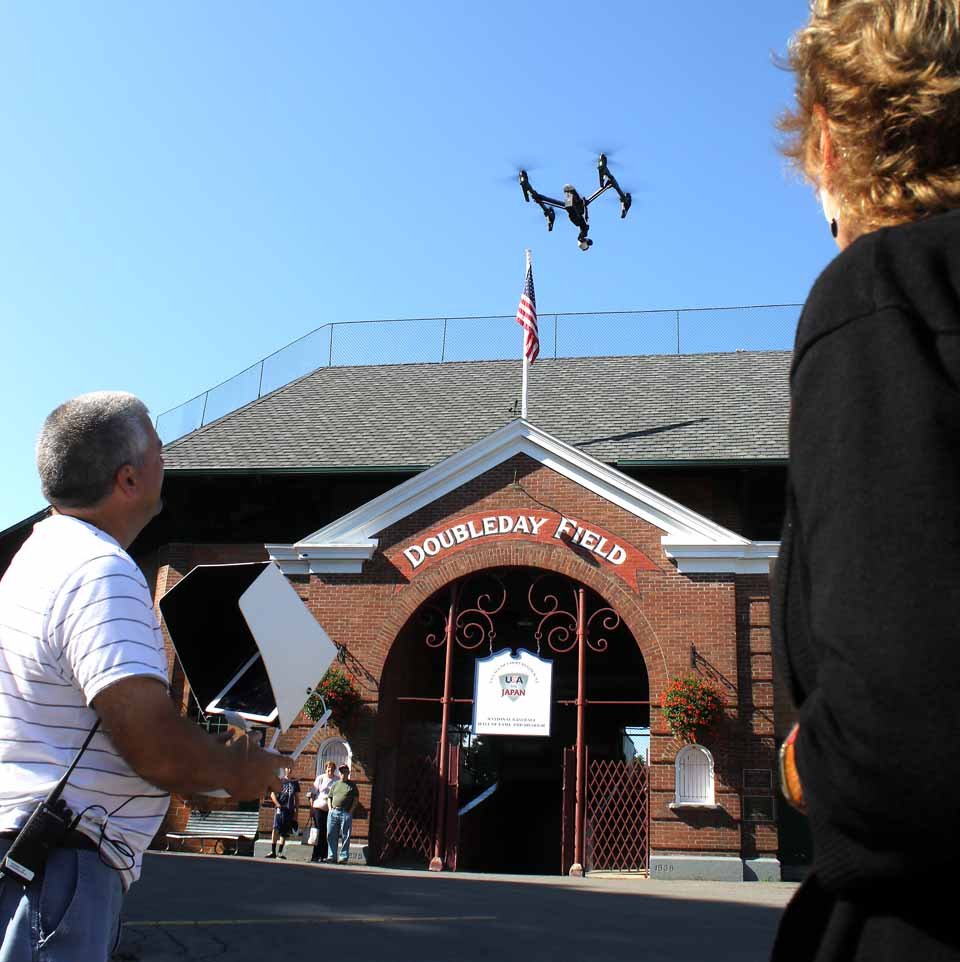 "Paul Frederick of Adworkshop, Lake Placid, launches a drone over Doubleday Field a few minutes ago, which is shooting footage of ""The Birthplace of Baseball"" in preparing new web and social media videos for Destination Marketing Corp. of Otsego County, the county's tourism promotion effort. DMOC's director, Deb Taylor, left, said the Adworkshop team will be in the county through Thursday; the drone will be buzzing over Hyde Hall tomorrow, and other shoots are still being arranged. (Jim Kevlin/allotsego.com)"